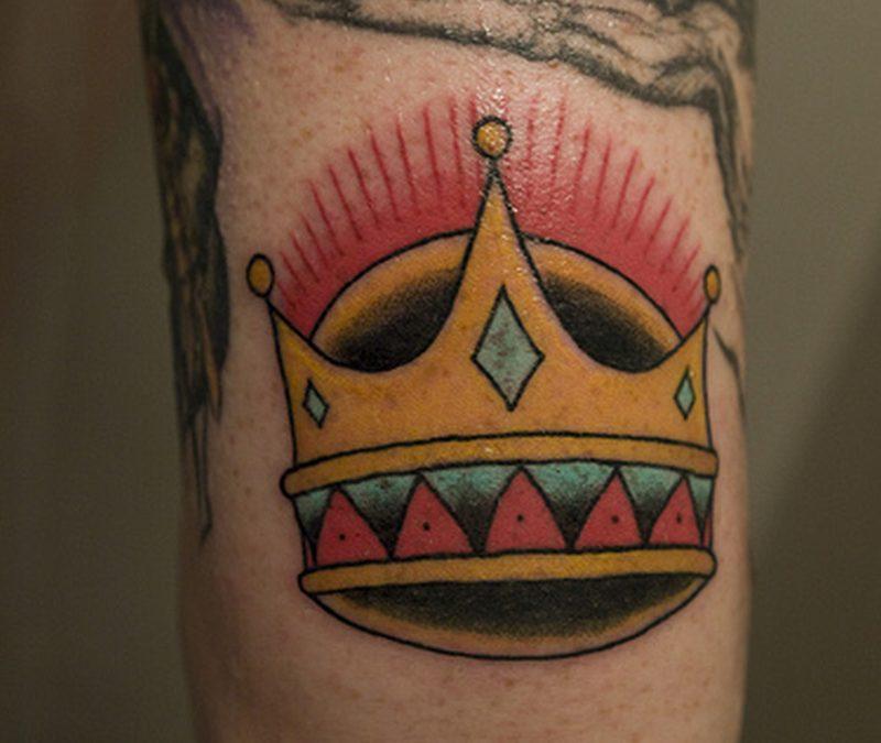 Crown tattoo near elbow