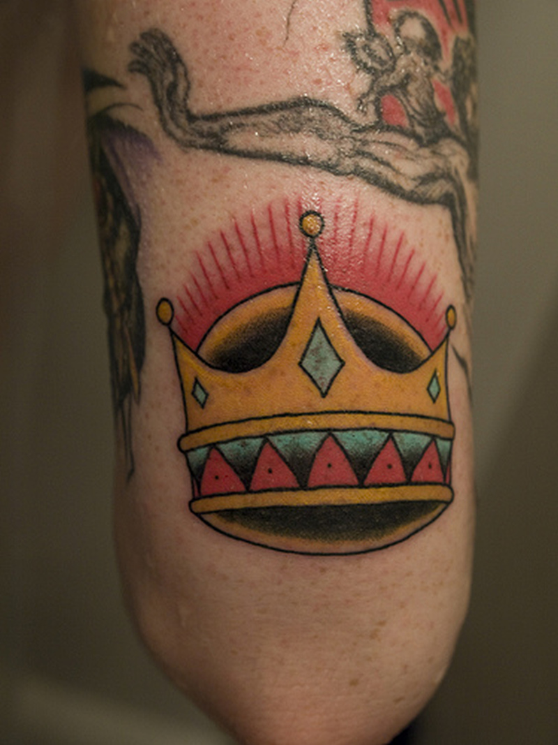 Crown tattoo near elbow
