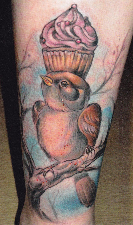 Cup cake tattoo on bird head tattoo design