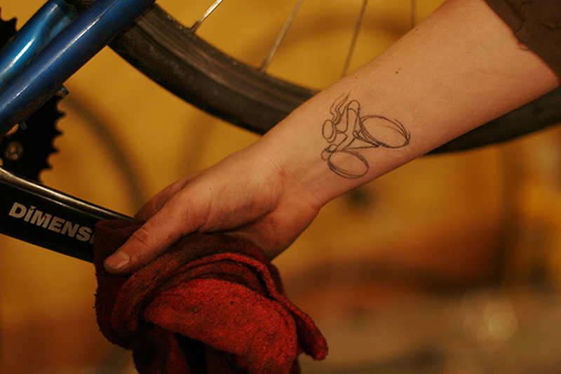 Cycle outline tattoo on wrist