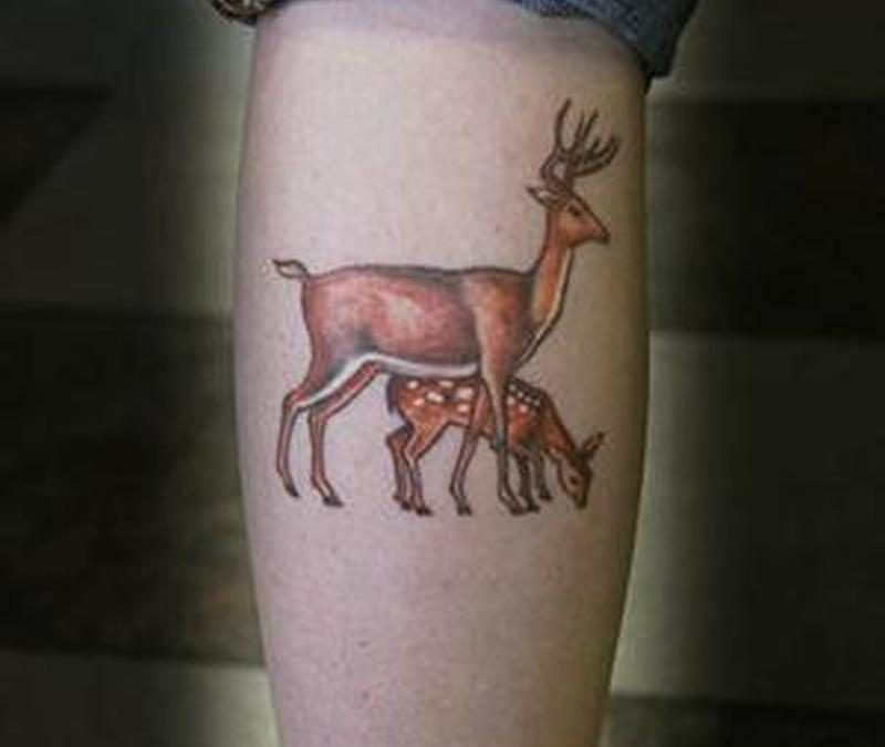 Deer with baby tattoo on leg