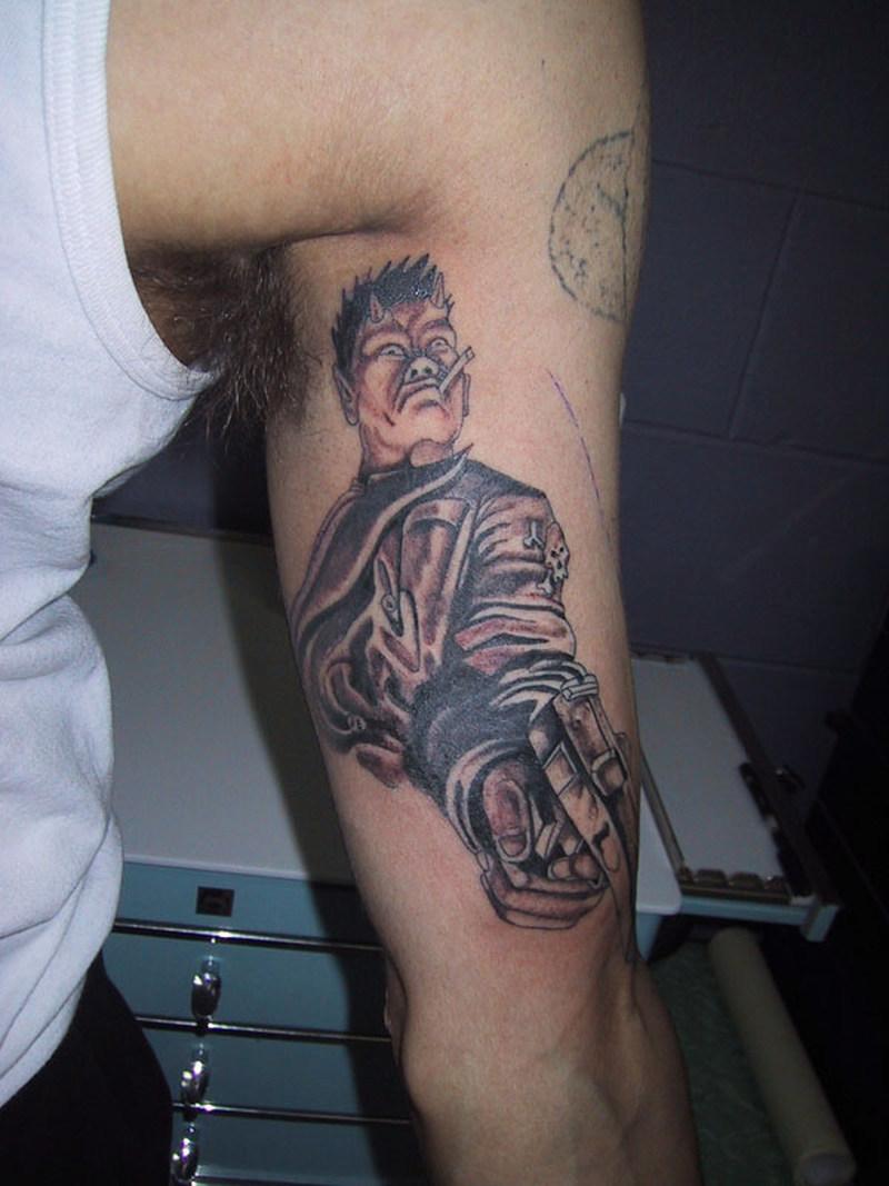 Devil with gun inner biceps tattoo