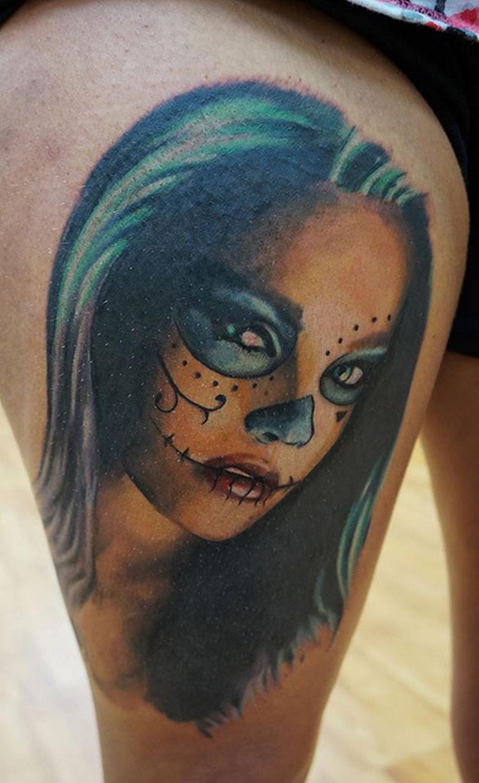 Dia de los muertos face tattoo on right thigh