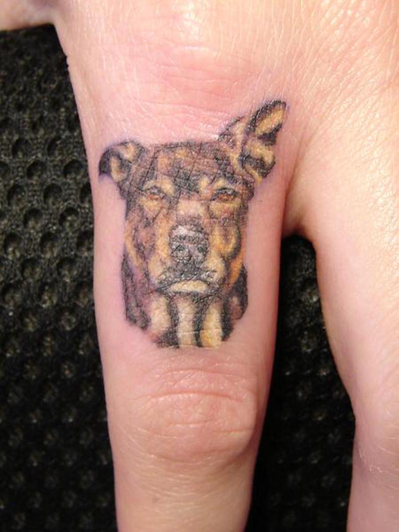 Dog face tattoo on finger