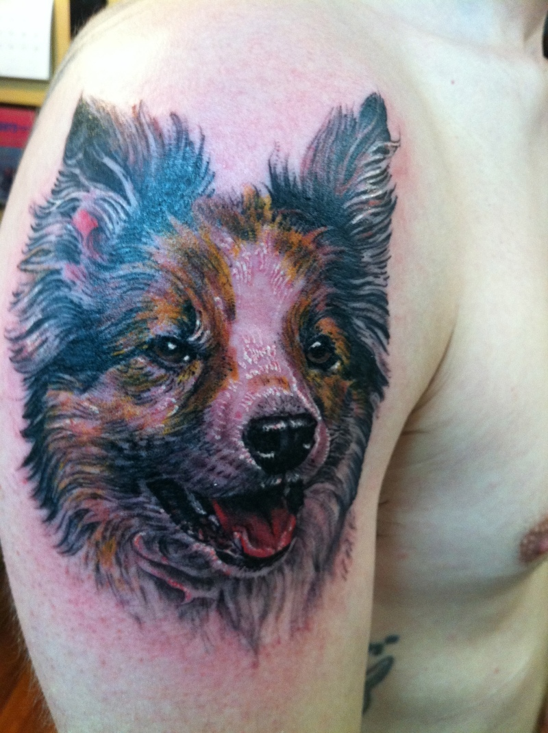 Dog face tattoo on shoulder