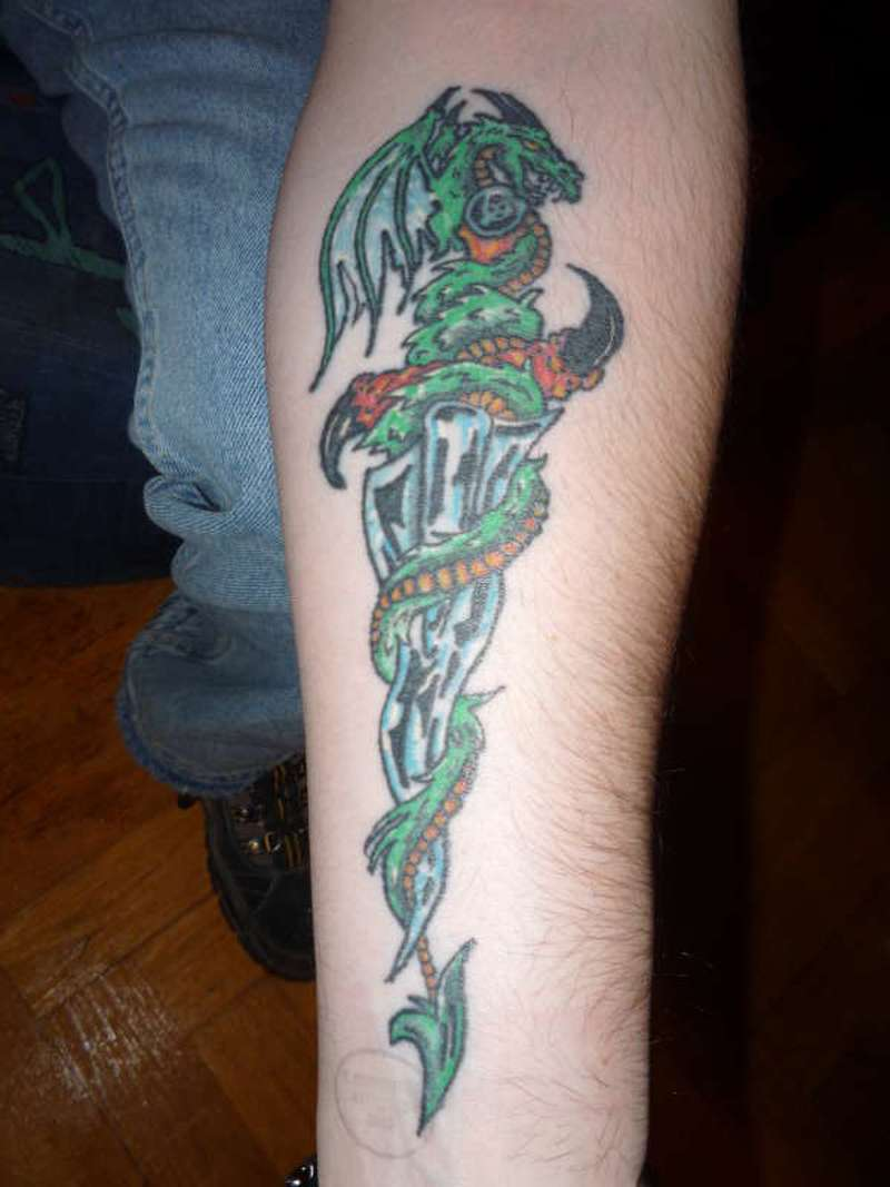 Dragon around dagger on forearm tattoo
