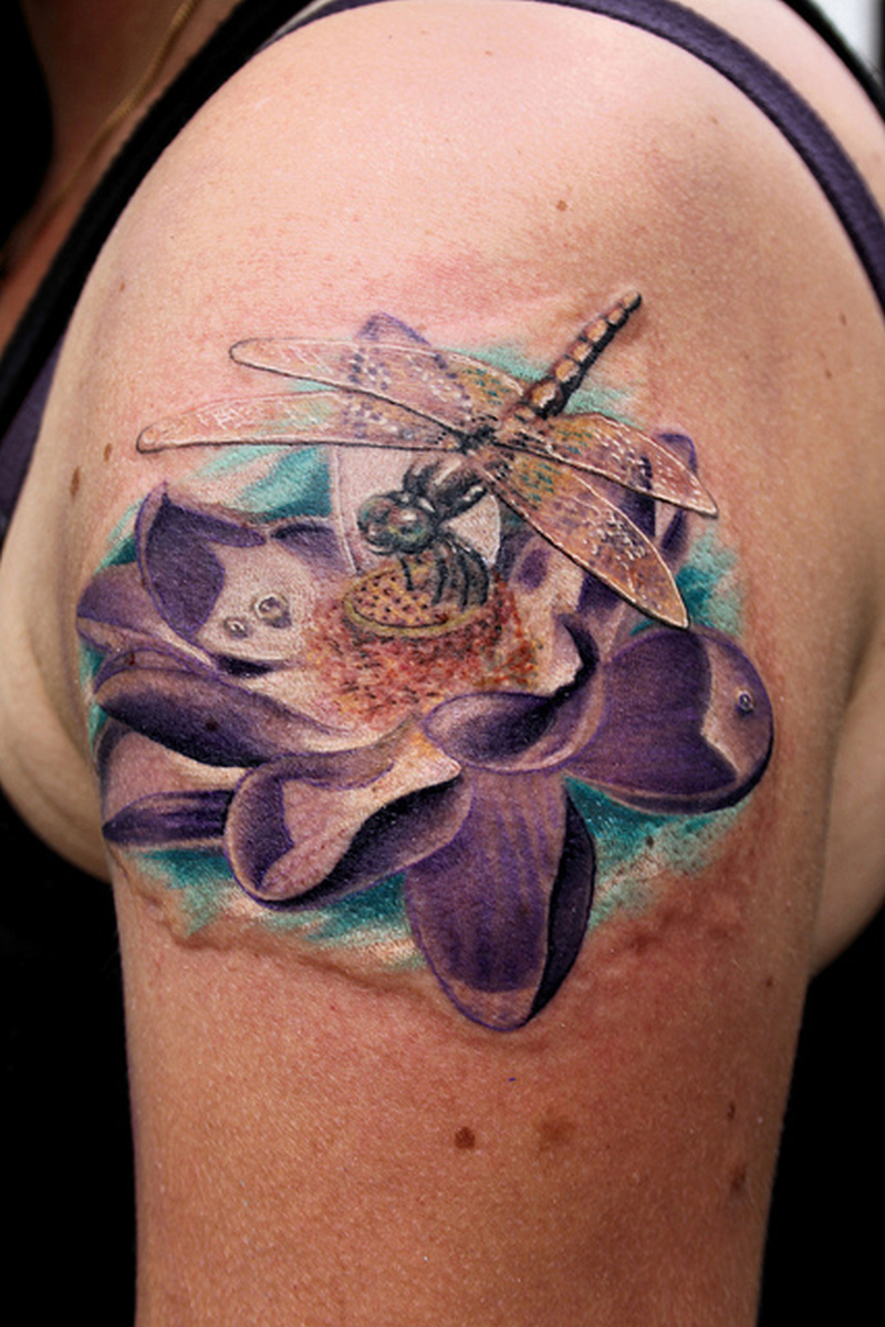 Dragonfly with lotus tattoo on upper arm