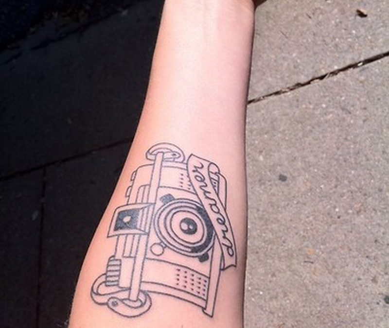 Dreamer camera tattoo on forearm