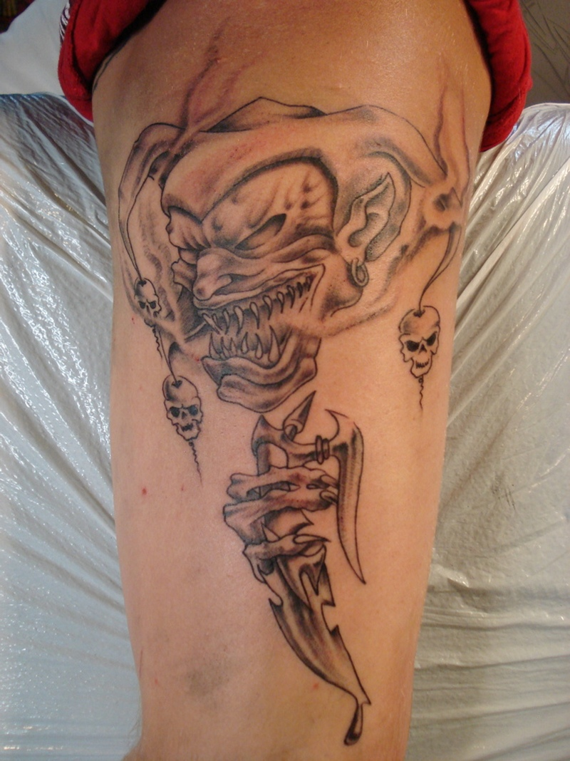 Evil jester joker tattoo on arm