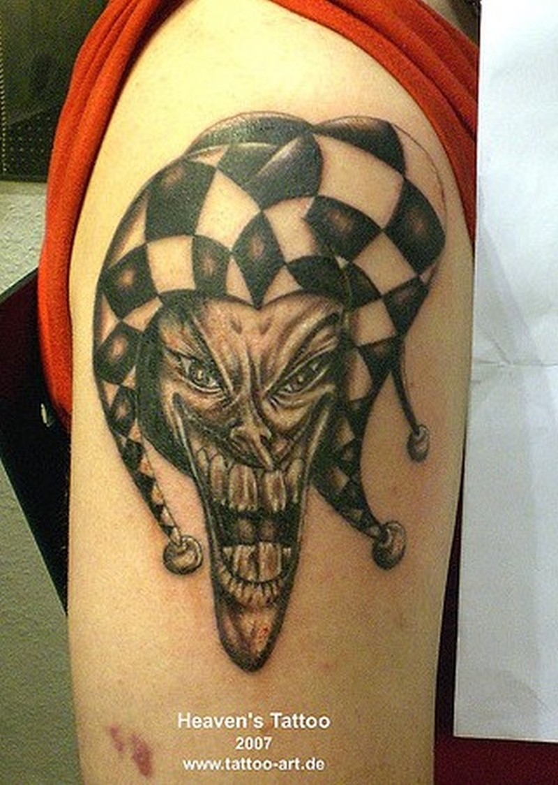 Evil joker clown on arm tattoo