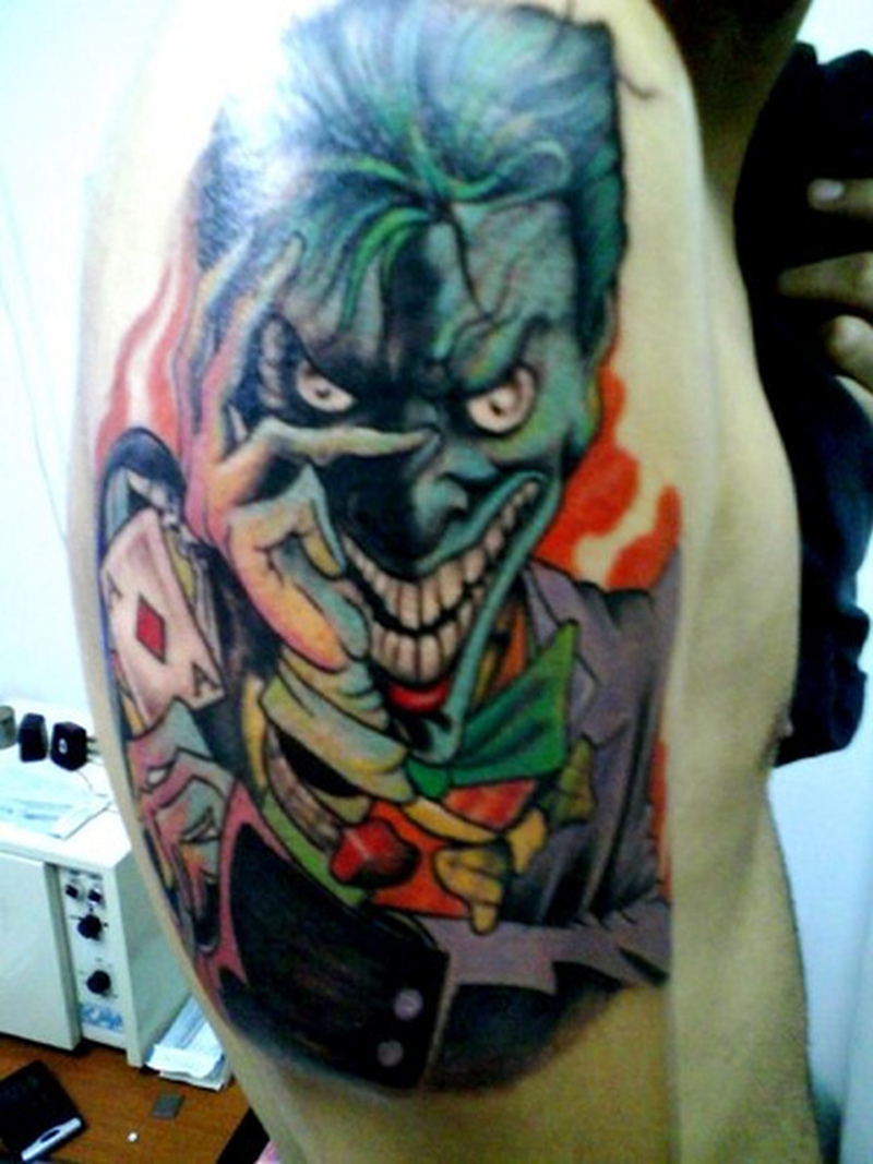 Evil joker with card tattoo on arm