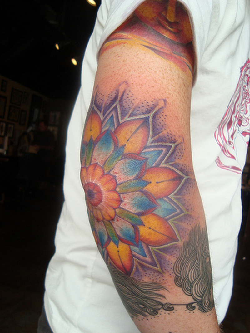 Extreme flower tattoo on right elbow