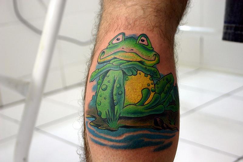 Fat cartoon frog on calf tattoo