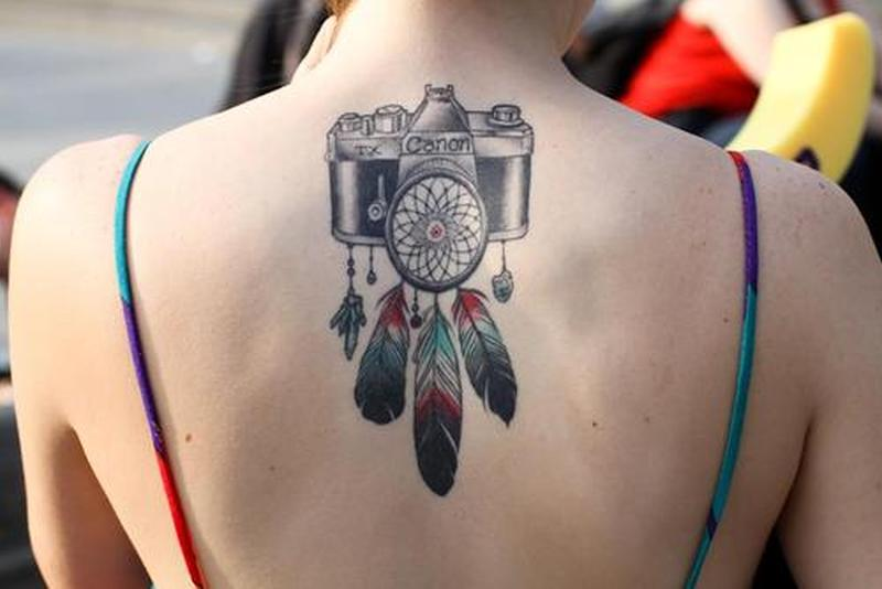 Feather camera tattoo on upper back for girls