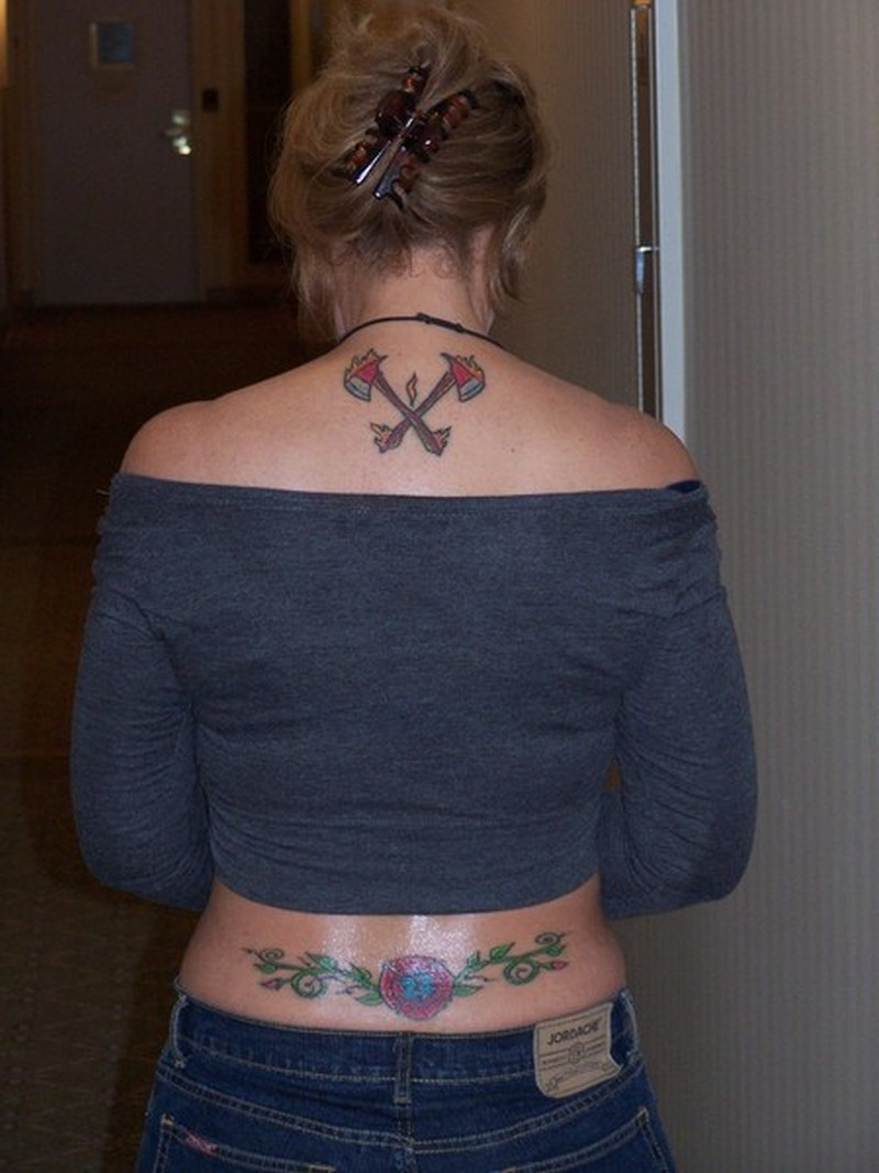 Firefighter tattoo on upper back of woman