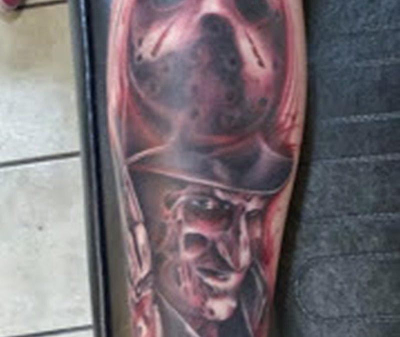Freddy vs jason horror tattoo on arm