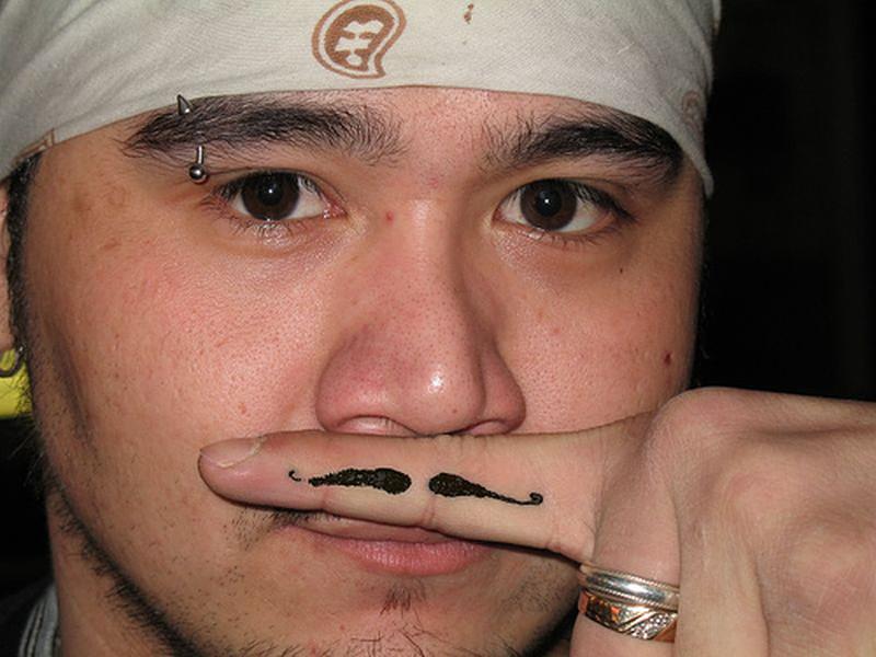 Funny moustache tattoo on finger