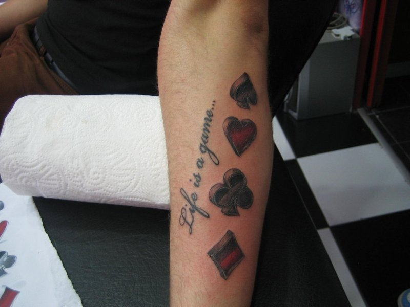 Gambling symbols tattoo on arm