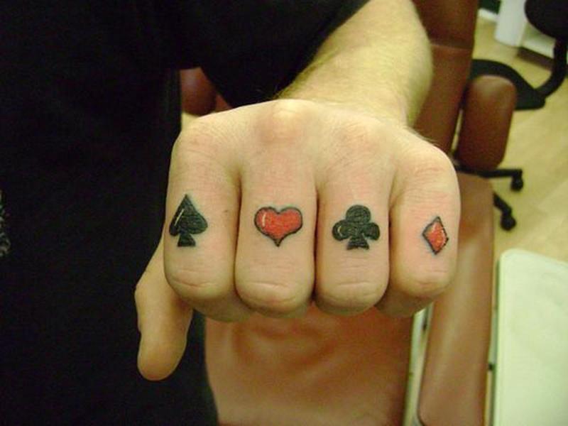 Gambling symbols tattoo on knuckle