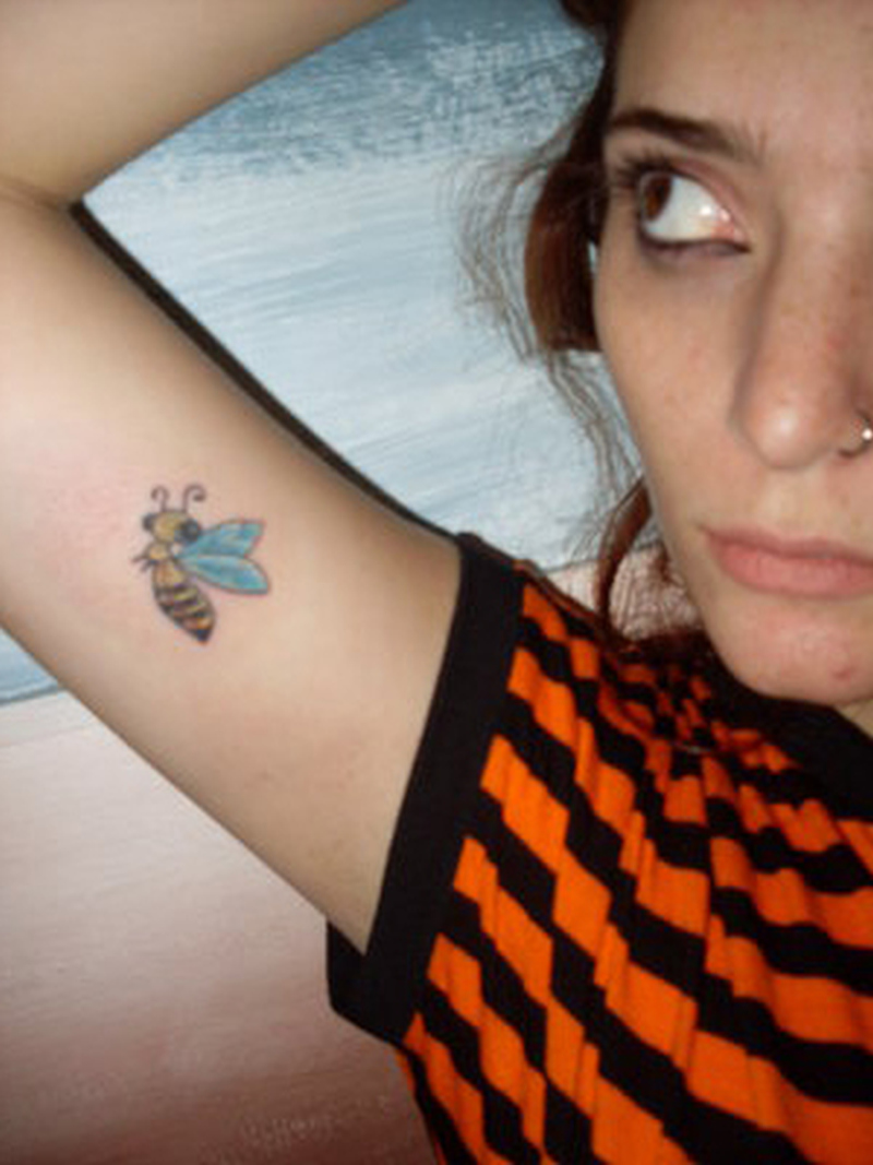 Girl with bumblebee tattoo on muscles