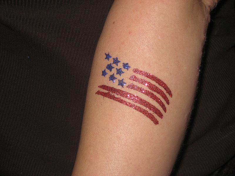 Glitter flag tattoo on arm