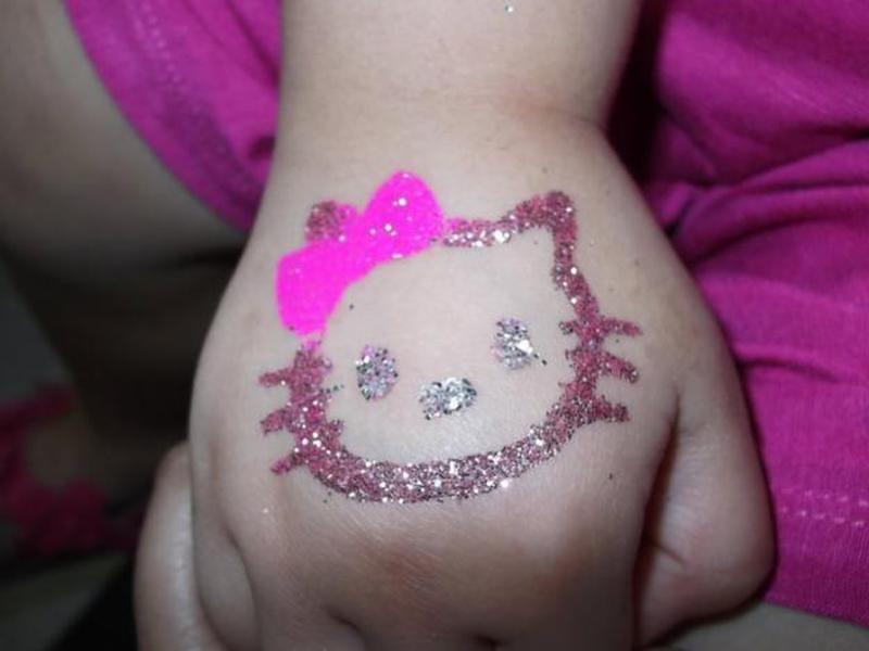 Glitter hello kitty face tattoo on hand