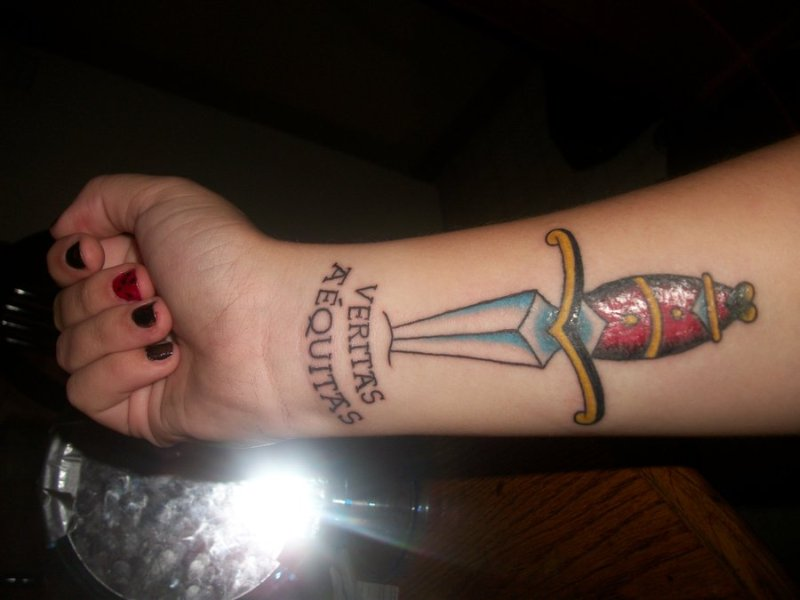 Glowing dagger tattoo on right forearm