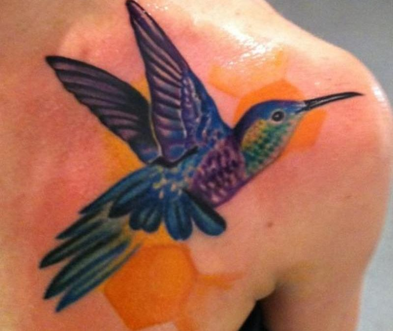 Glowing hummingbird tattoo on front shoulder