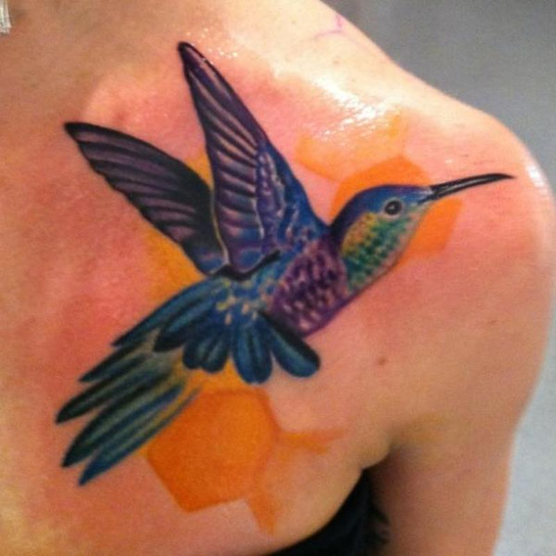 Glowing hummingbird tattoo on front shoulder