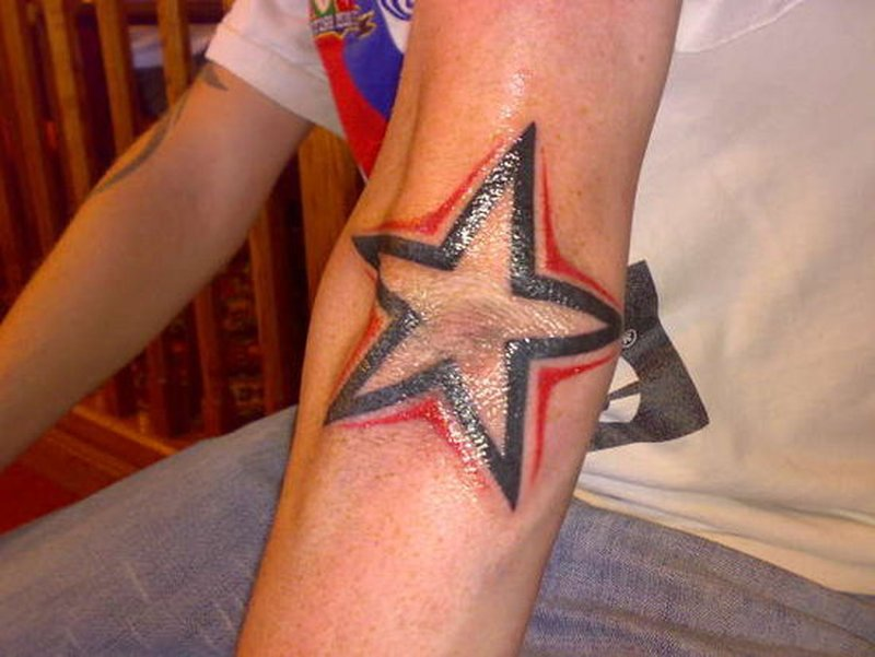 Glowing star tattoo on elbow