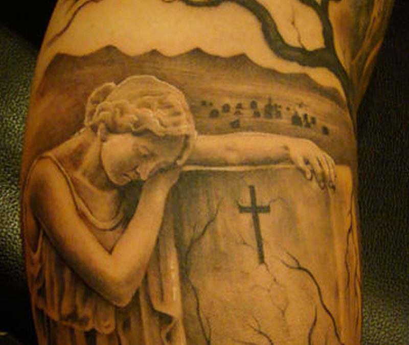 Graveyard on muscles tattoo
