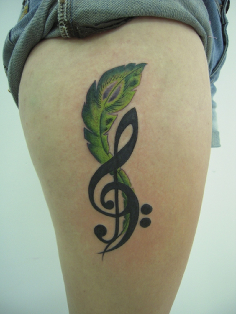 Green feather n music note tattoo on right thigh