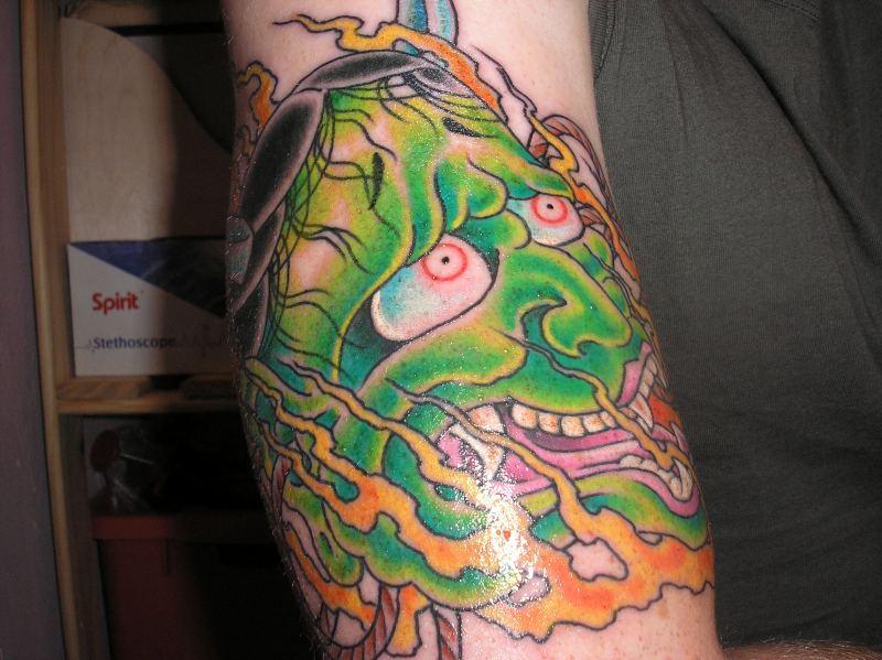 Green ink asian demon face tattoo design