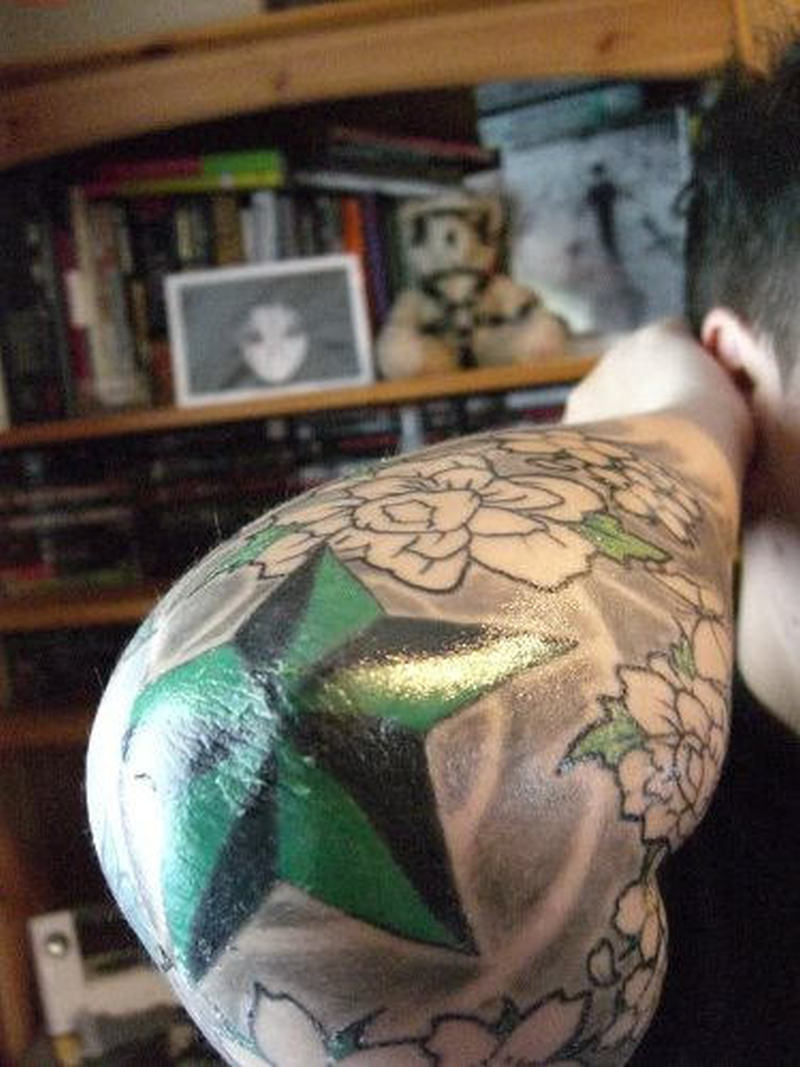 Green nautical star tattoo on elbow