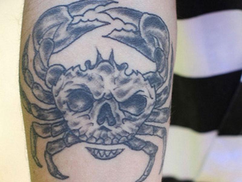 Grey ink cancer tattoo on arm