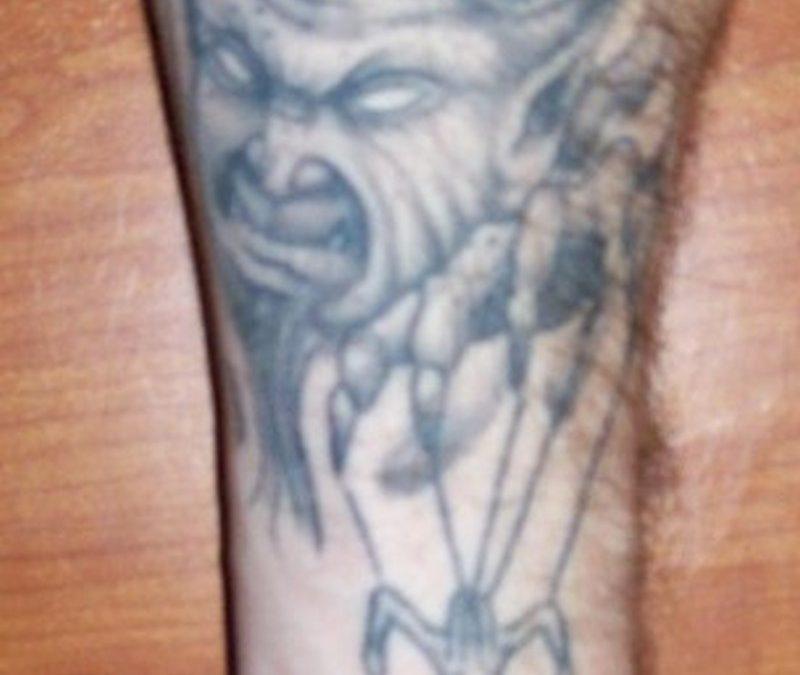 Grey ink devil tattoo on forearm