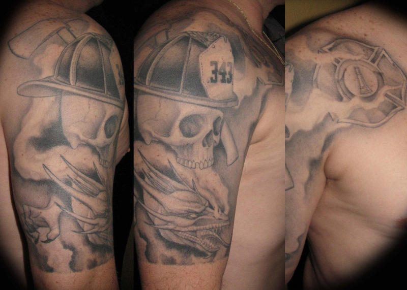 Grey ink firefighter skull tattoo on shoulder