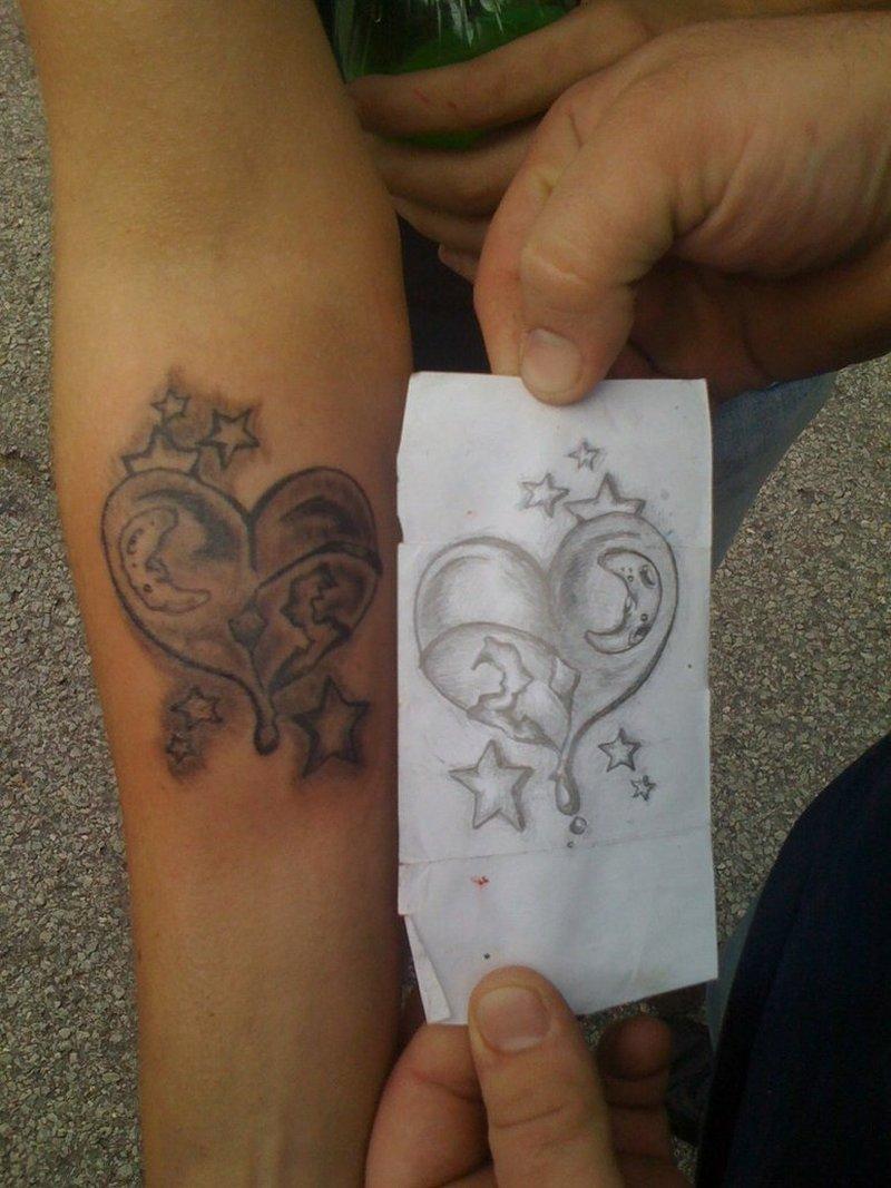 Grey ink heart n stars tattoo on forearm