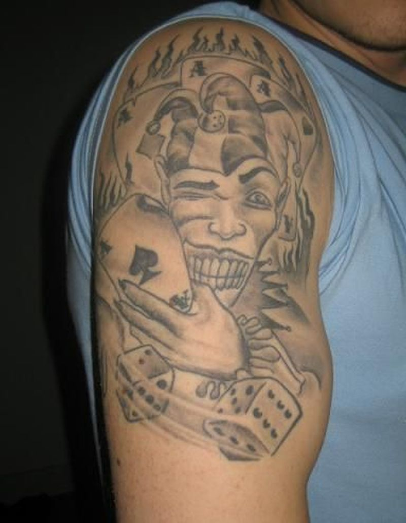 Grey ink joker n dice tattoo on upper arm