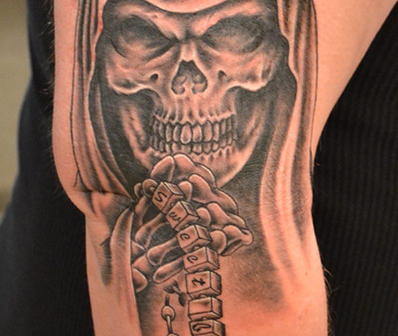 Grim reaper tattoo on elbow