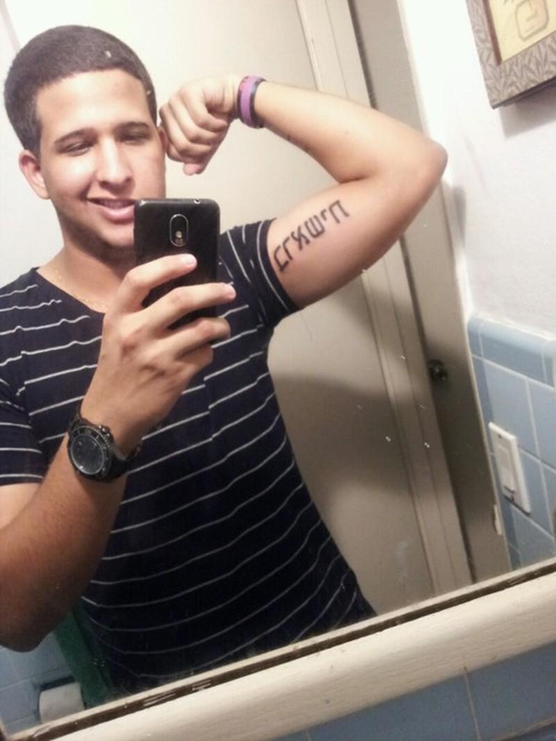 Hebrew script on muscles tattoo