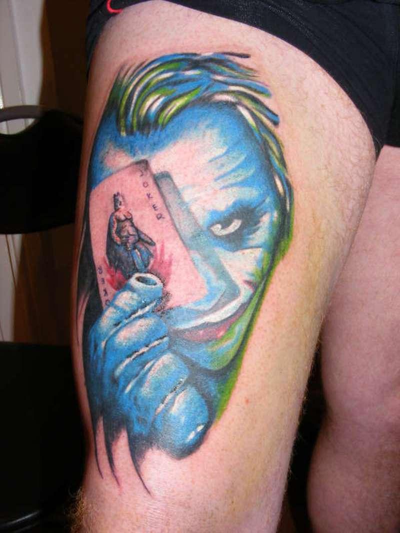 Joker eye card tattoo on right thigh