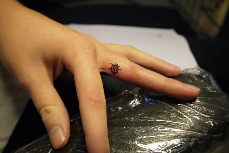 Lady bug tattoo on middle finger