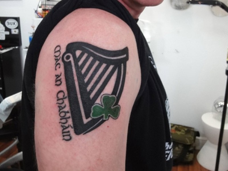 Lovely black ink music with green clover tattoo on shoulder