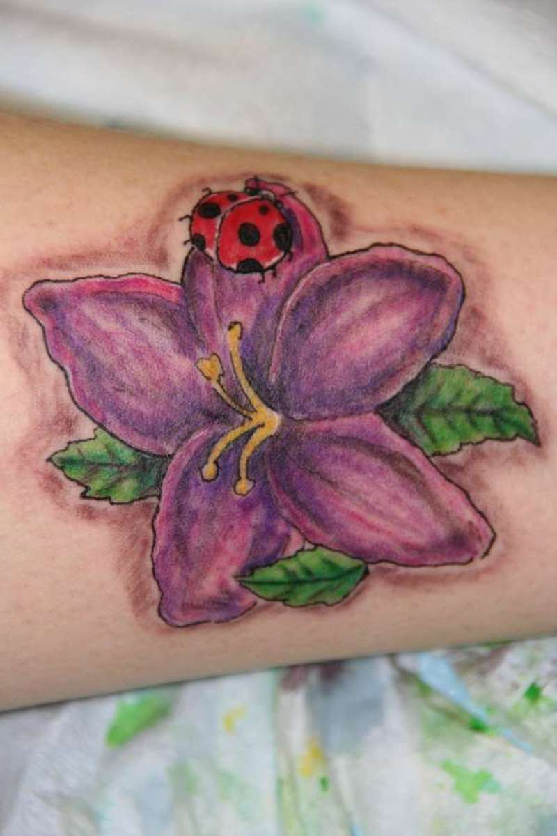 Lovely lady bug on flower tattoo design