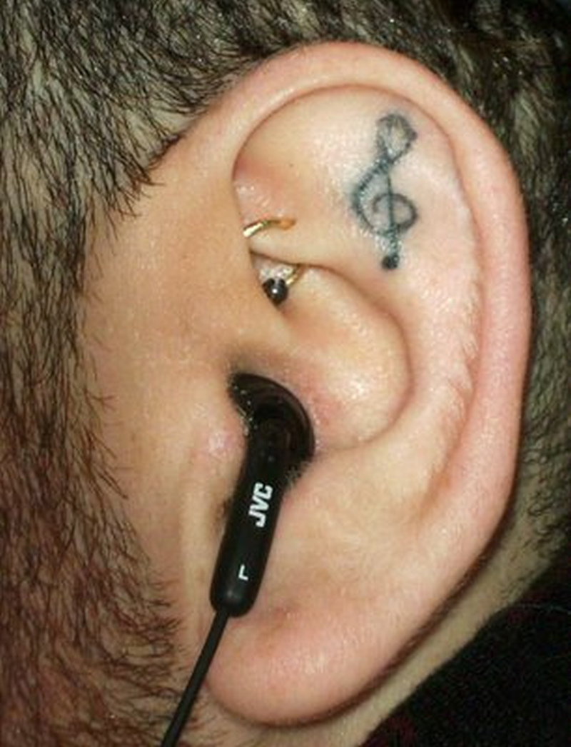 Music note in ear tattoo