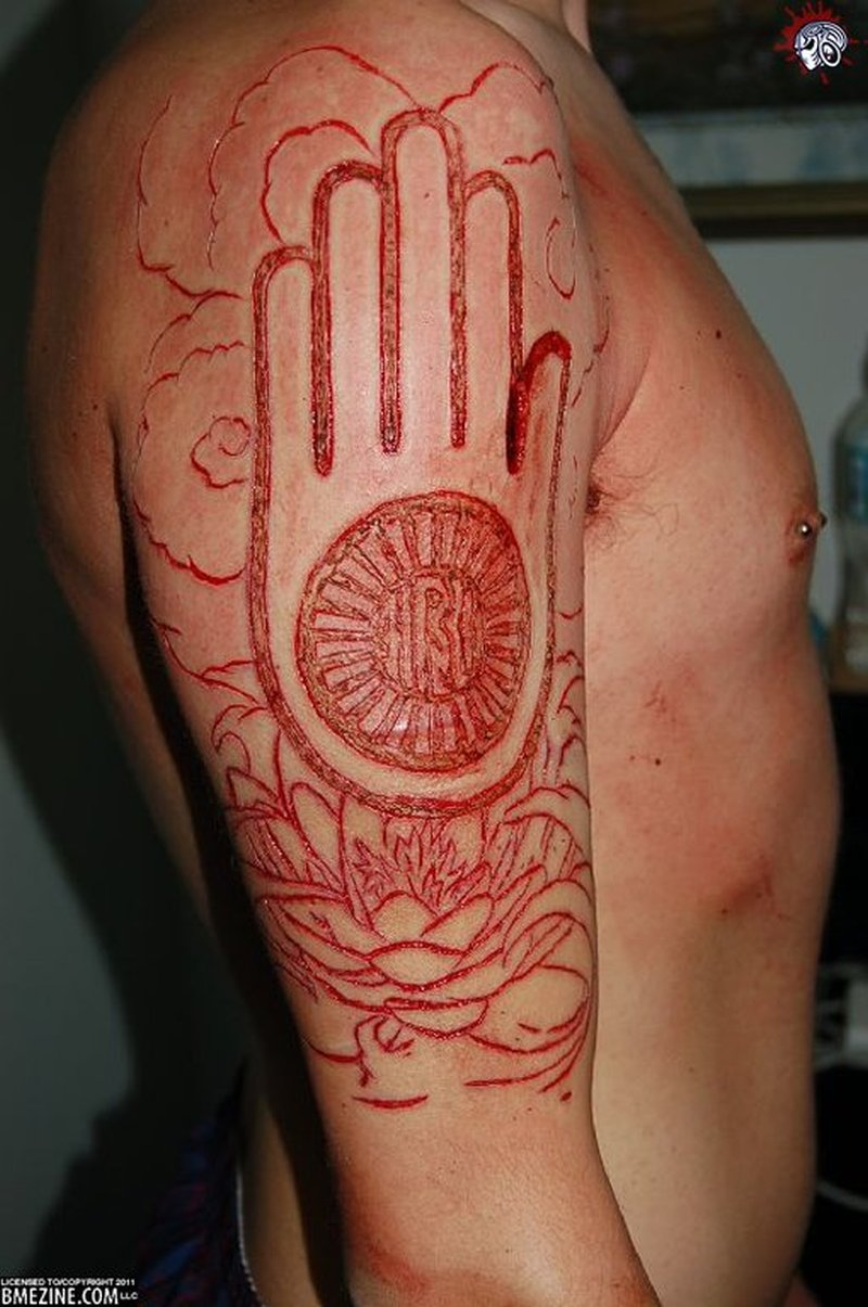 Red ink jain on half sleeve tattoo