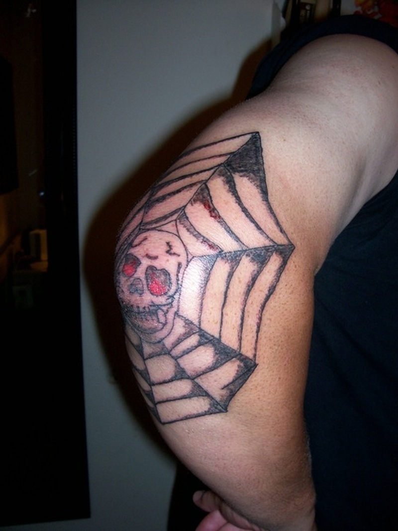 Skull with spider web tattoo on elbow