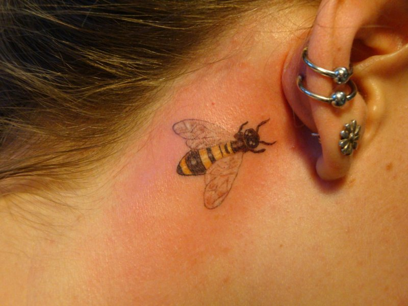 Small bumblebee tattoo on back ear