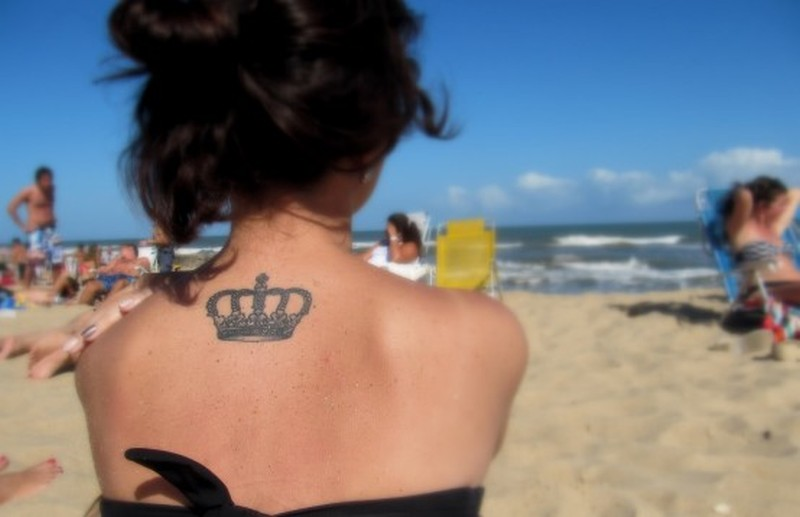 Small crown tattoo on upper back for girls